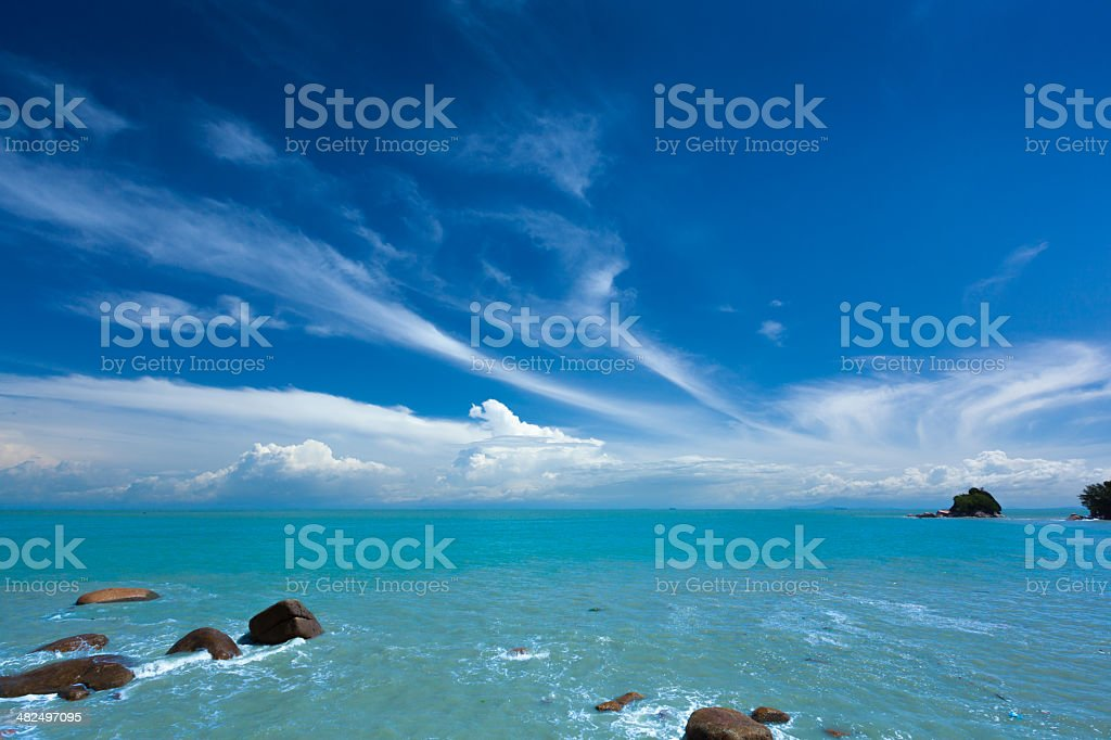 Rocky shore with blue sky and turquoise sea royalty-free stock photo