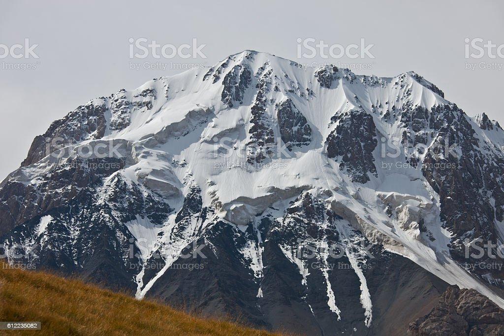 Rocky slope of mountain peaks, glaciers, snowfields stock photo
