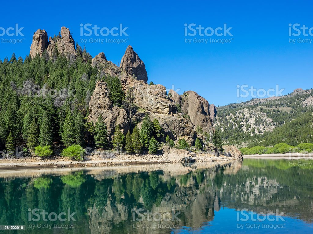 Rocky towers on hilltops reflected in the Rio Limay, Argentina. stock photo