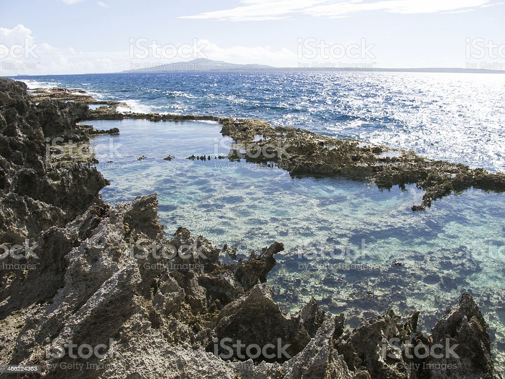 Rocky tropical tide pool with blue ocean stock photo
