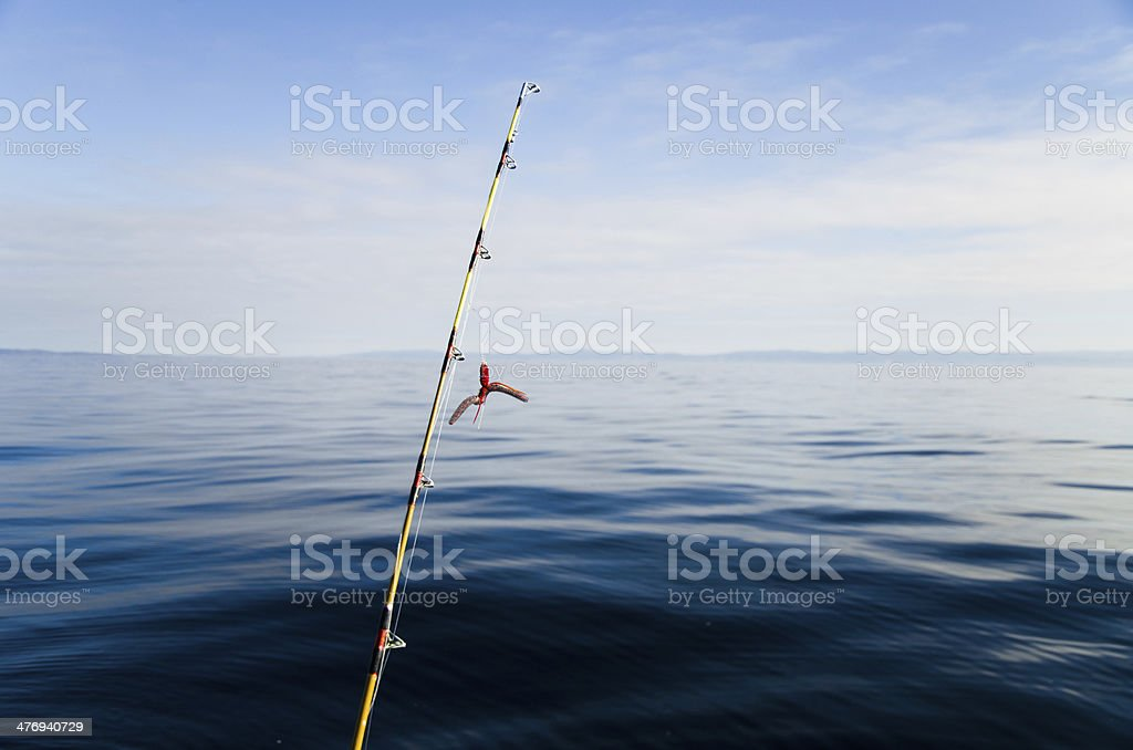 Rod for offshore ocean fishing looking into open blue sea. stock photo