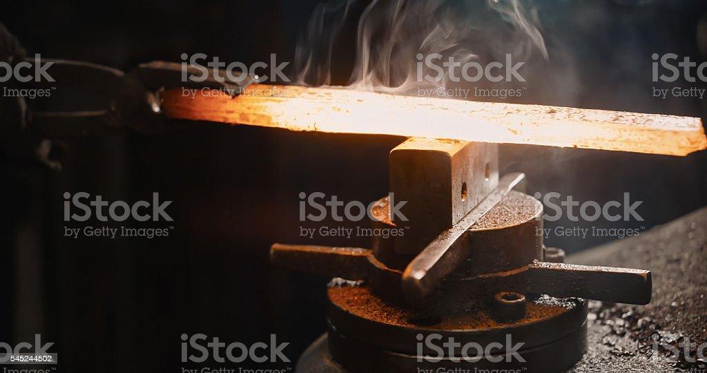Rod hot iron on the anvil. stock photo