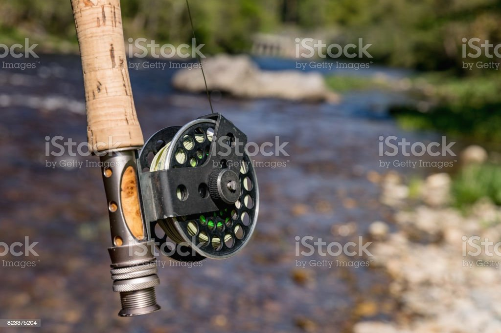 Rod with reel hunting trout. In the background, the trout river Otava, stock photo