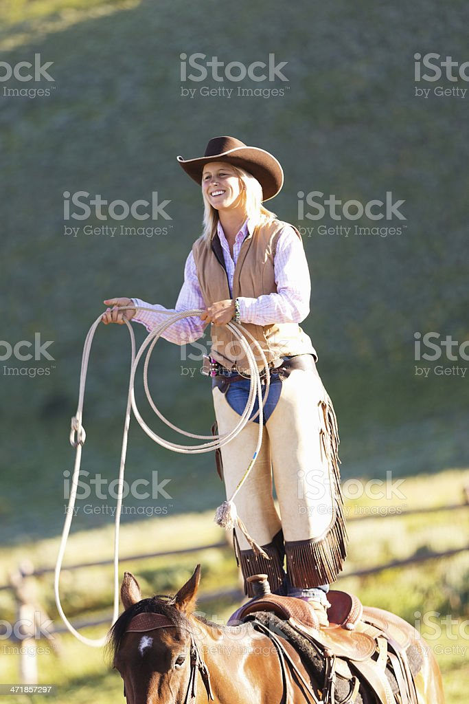 Rodeo cowgirl performing stunt on horseback with lasso royalty-free stock photo