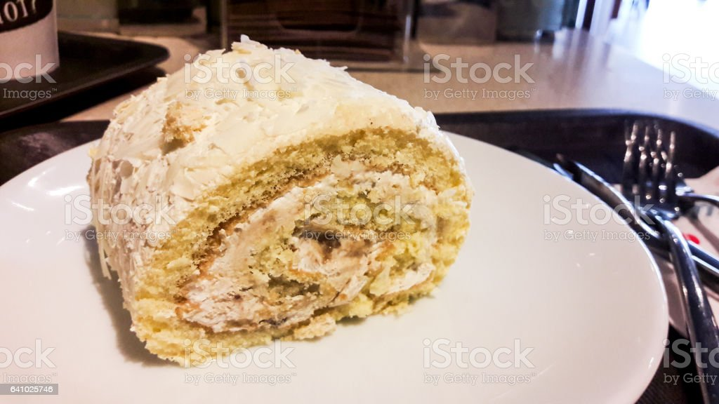 Roll cake in white plate with fork and knife at cafe stock photo