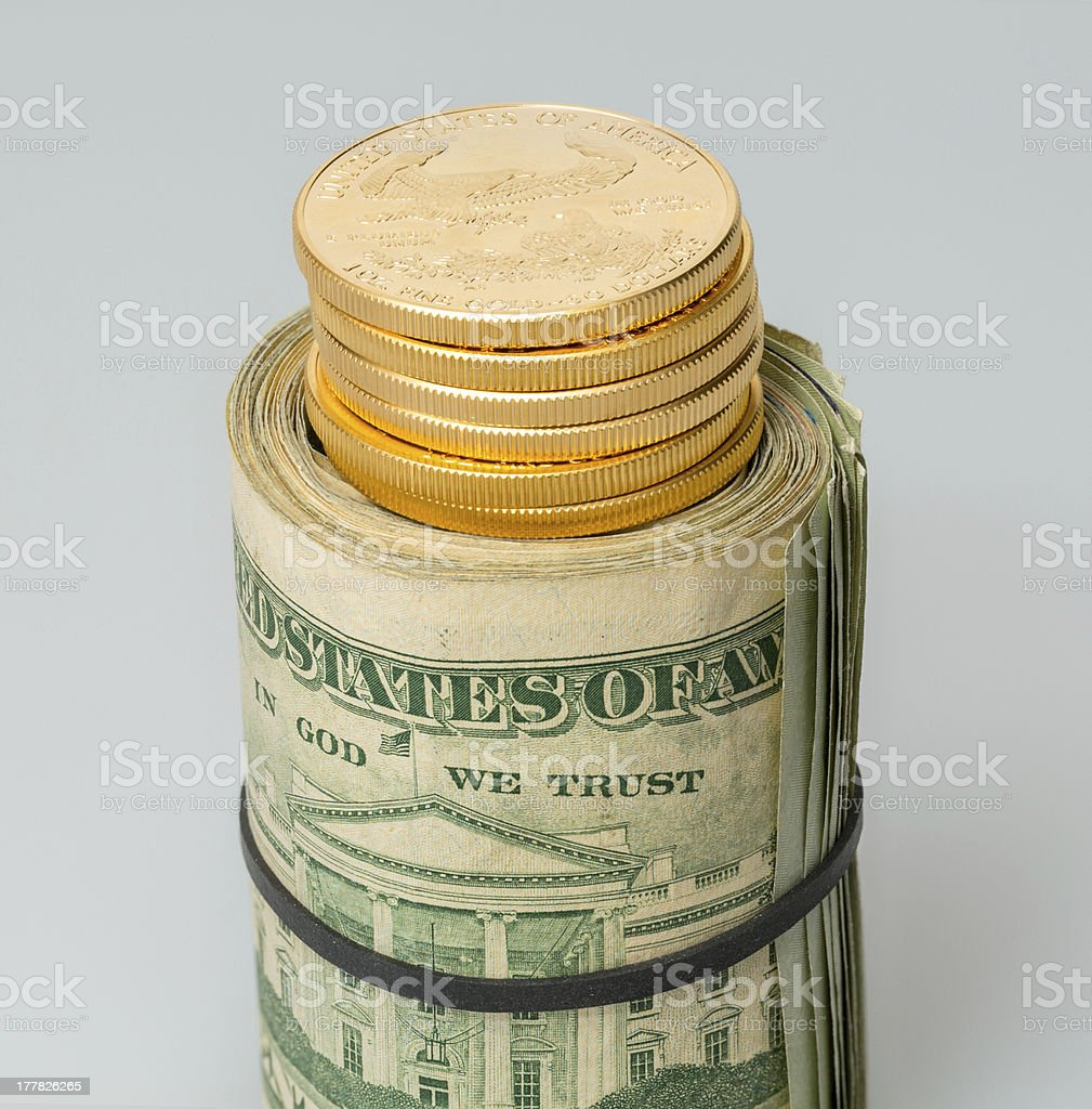 Roll of $20 dollar bills with gold coins royalty-free stock photo