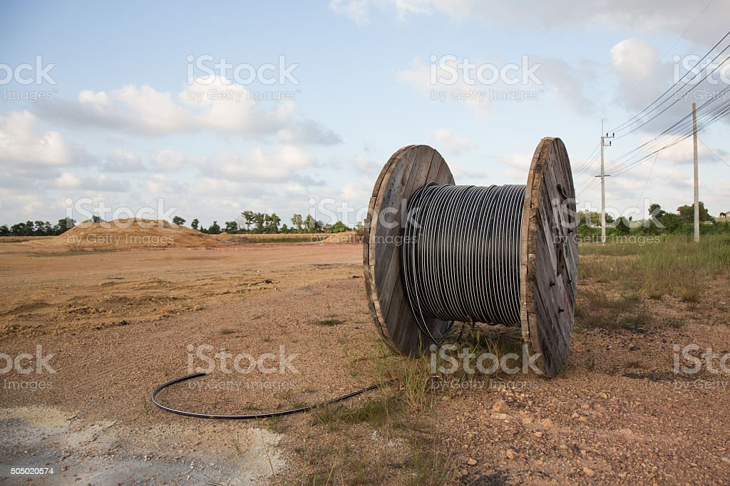 Roll of black industrial al cable with cross section stock photo