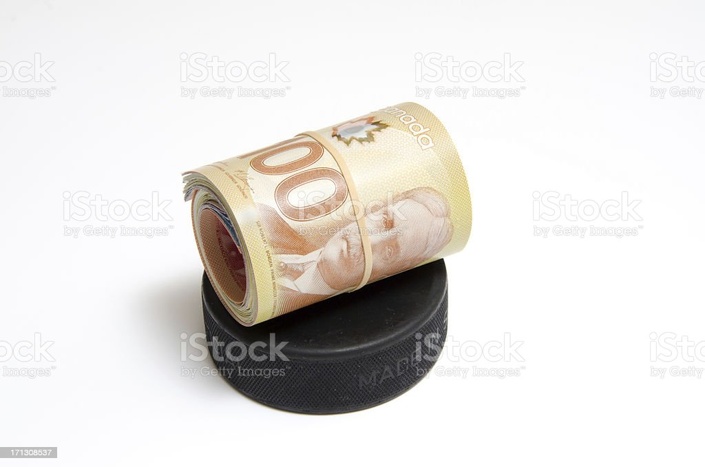 Roll of Canadian Money on a Hockey Puck stock photo