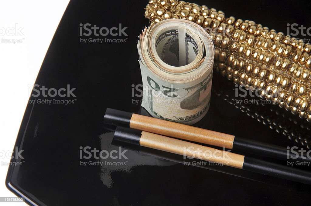 roll of dollar bills and  golden ear  on  black plate royalty-free stock photo