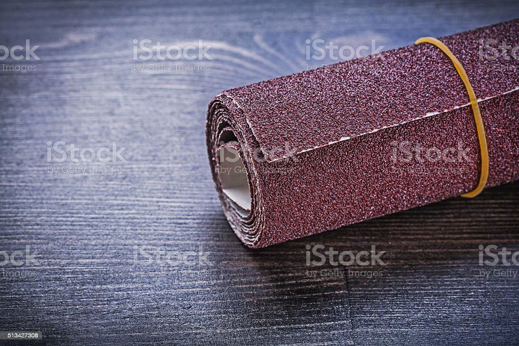 Roll of emery paper on vintage wooden board abrasive equipment stock photo