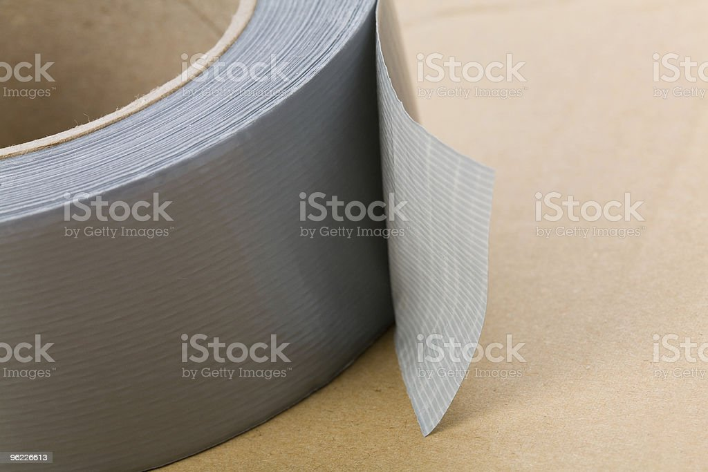 A roll of grey duct tape on a brown surface stock photo
