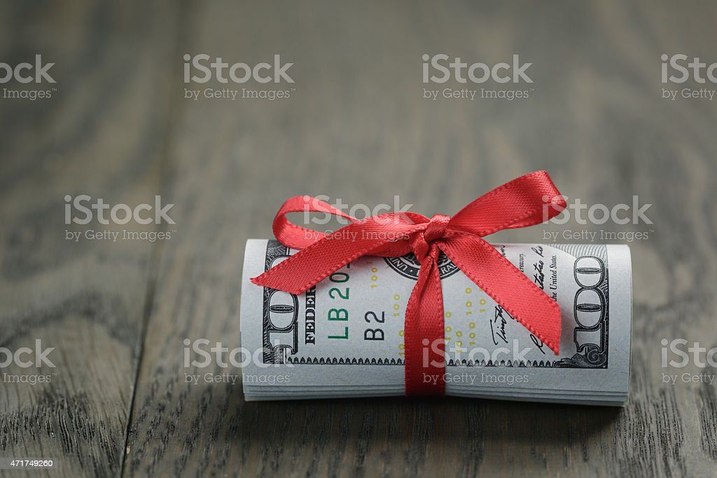 roll of hundred dollar bills on wooden table stock photo