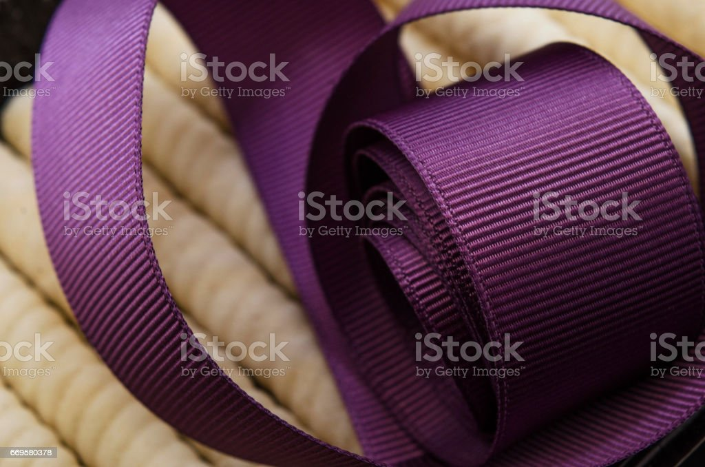 Roll of purple satin ribbon on sweets
