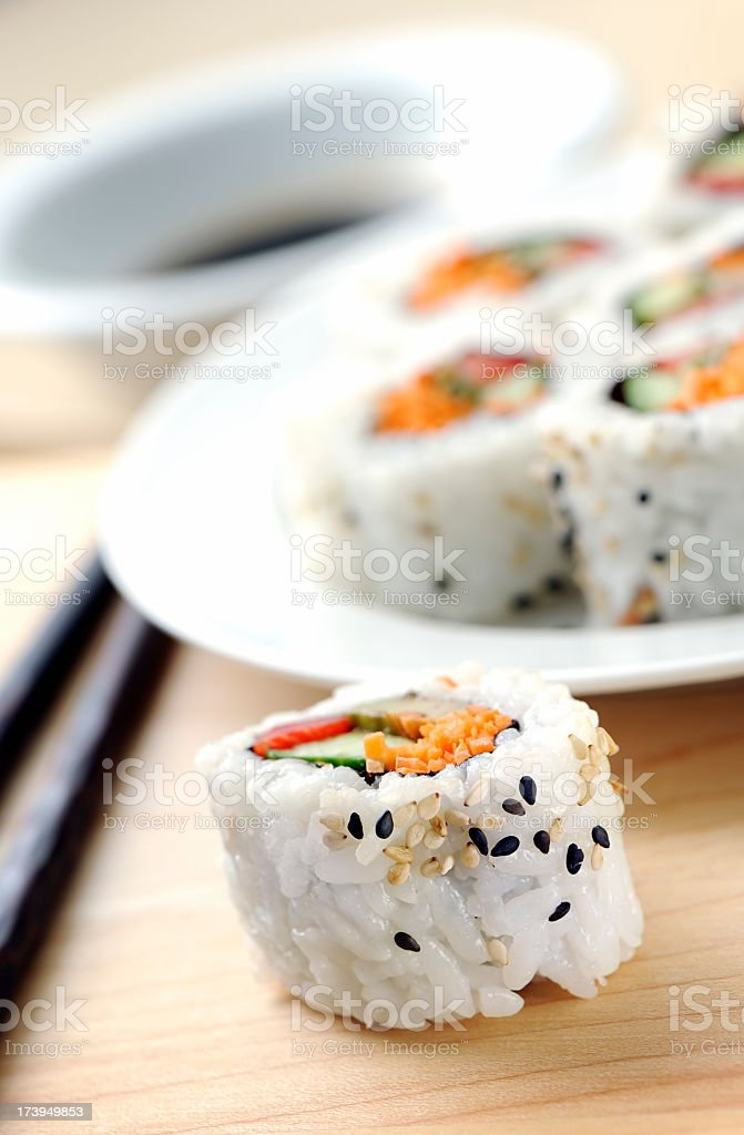 Roll of sushi off sitting beside a plate royalty-free stock photo
