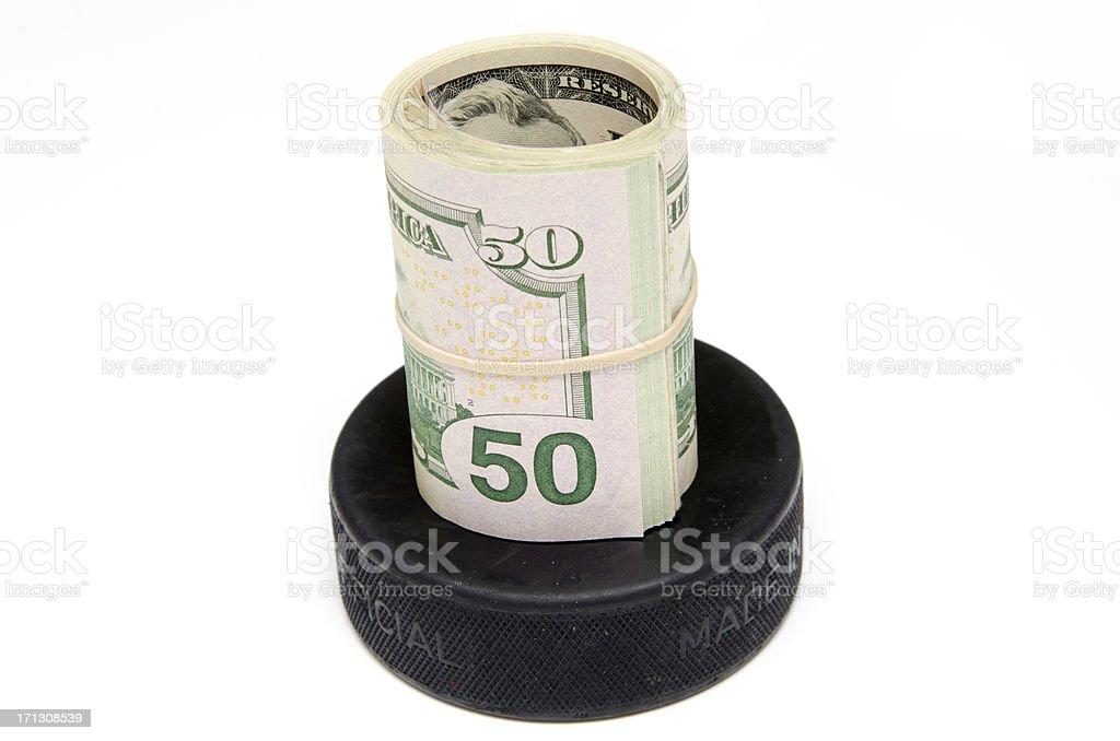 Roll of US Money on a Hockey Puck royalty-free stock photo