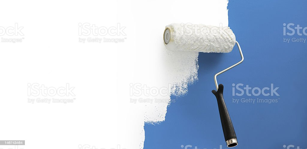 Roll of white paint going over previous blue paint royalty-free stock photo