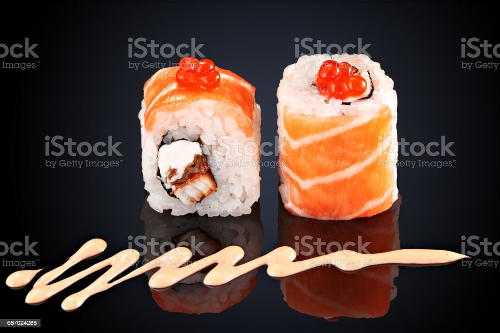 Roll salmon, eel, caviar, cream cheese and spicy sauce stock photo