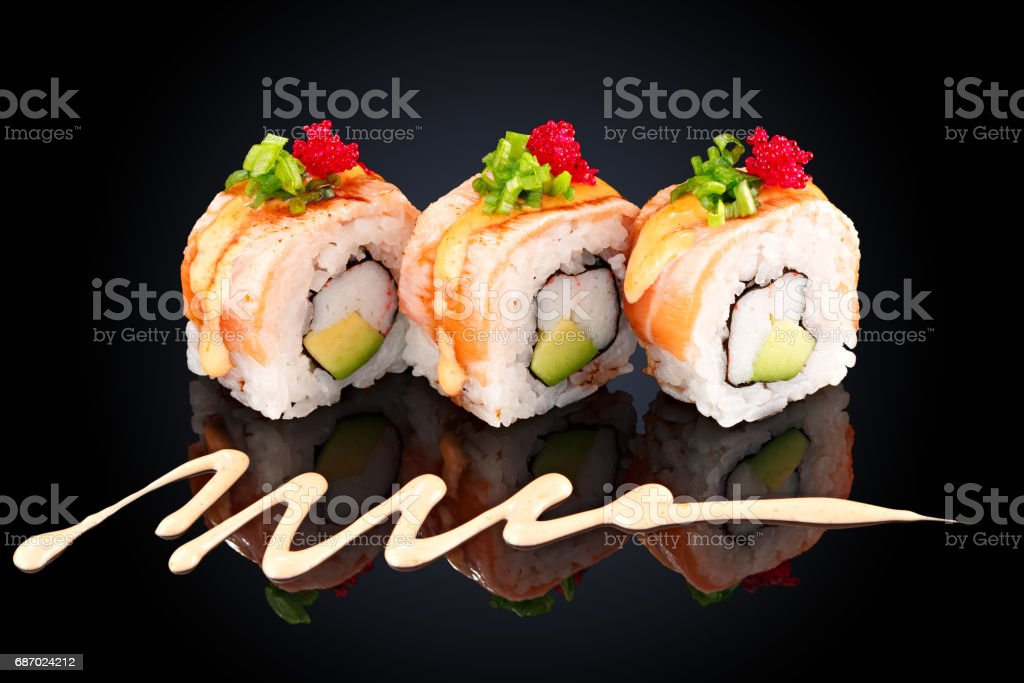 Roll with eel, crab, avocado, cream cheese and spicy sauce stock photo