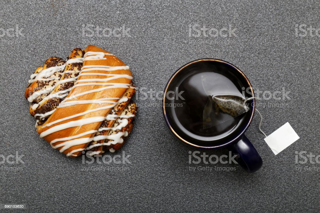 Roll with poppy decorated with white icing and a mug of tea stock photo