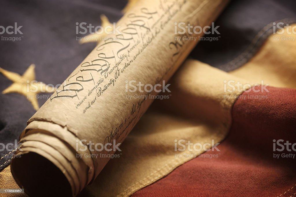 Rolle U.S. Constitution siting on an old American flag stock photo
