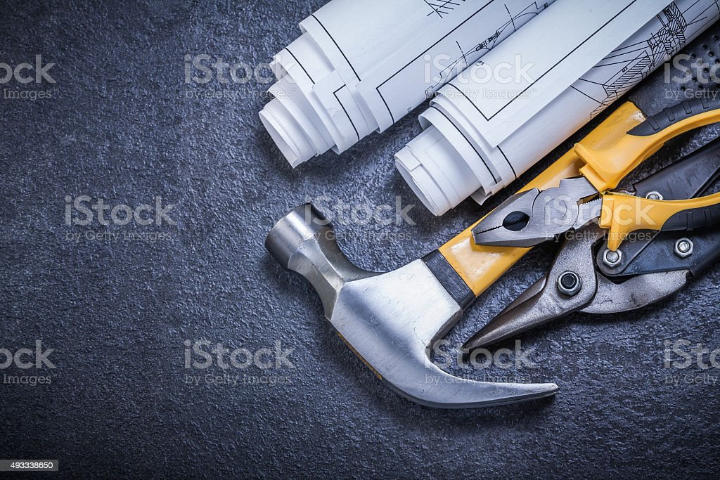 Rolled blueprints steel cutter pliers claw hammer on black backg stock photo