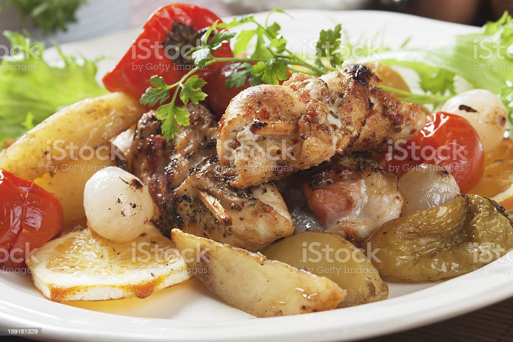 Rolled chicken skewer roasted with potatoes and vegetables royalty-free stock photo