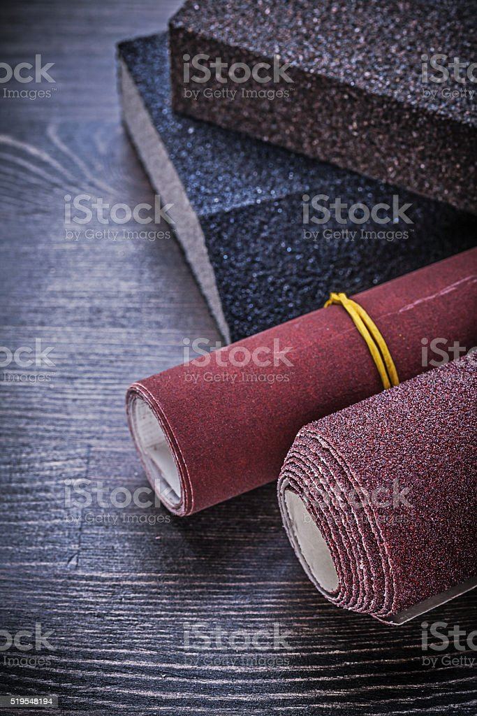 Rolled emery paper sanding sponges on vintage wooden board abras stock photo