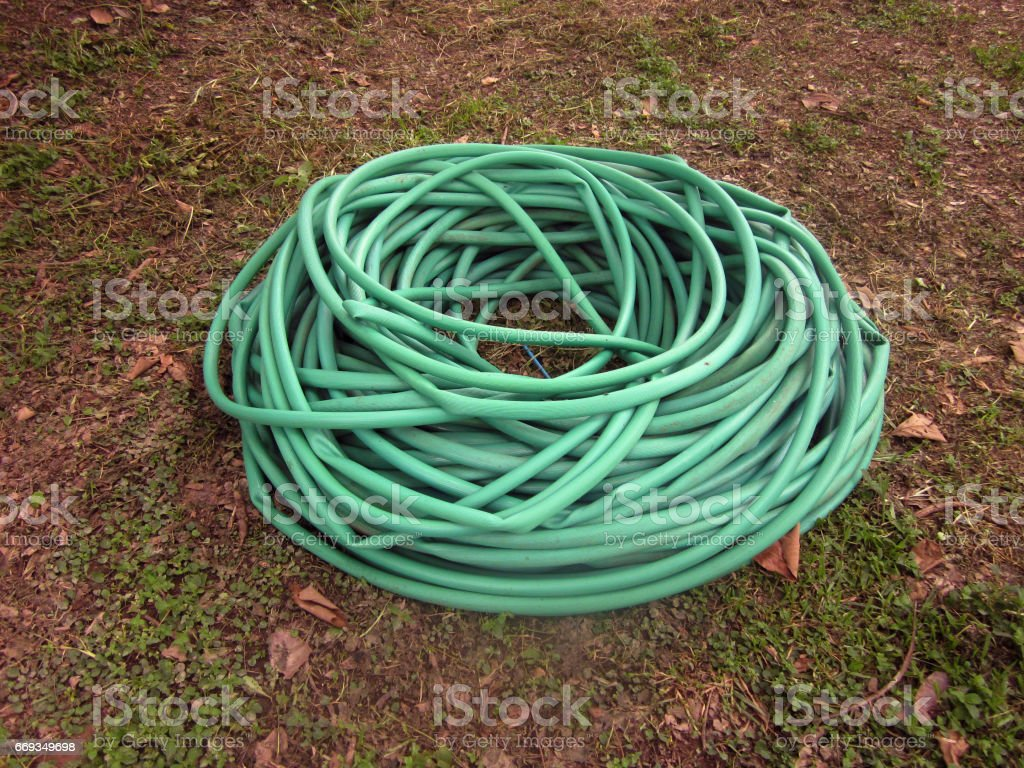 Rolled long garden hose on ground. stock photo