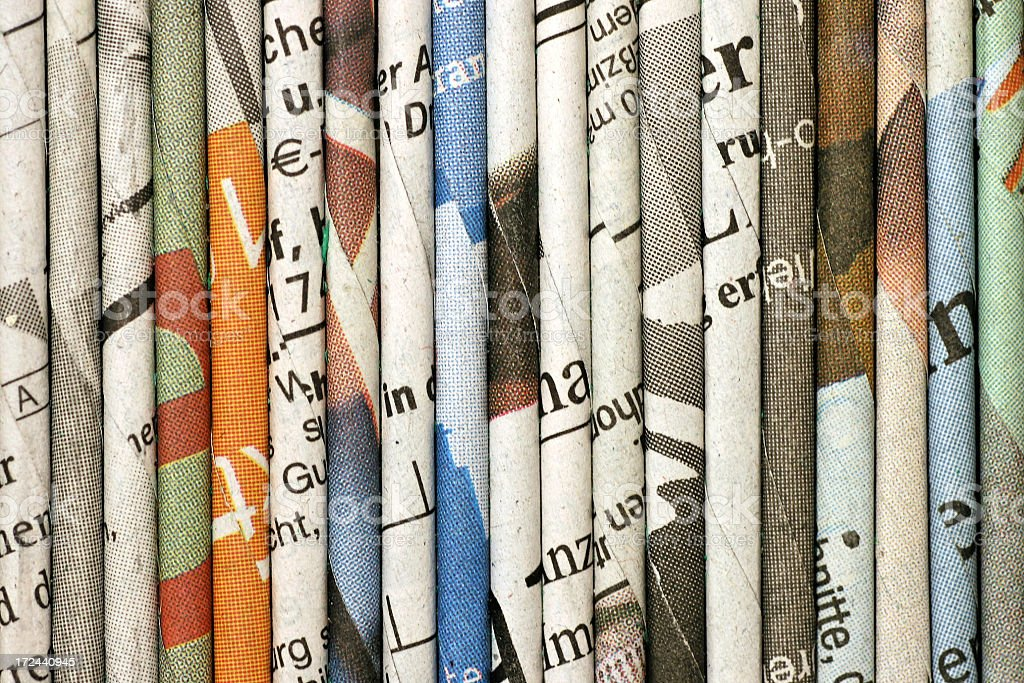 rolled newspaper pages stock photo