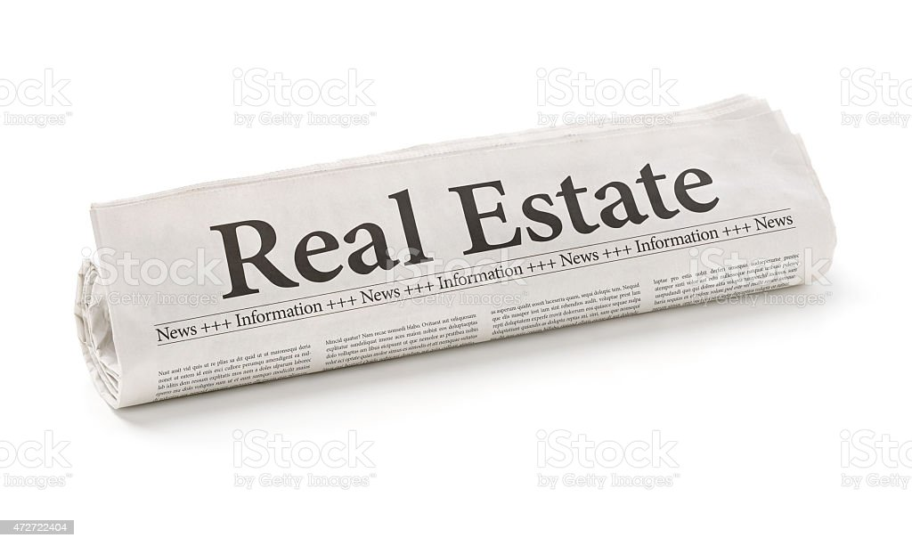 Rolled newspaper with the headline Real Estate stock photo