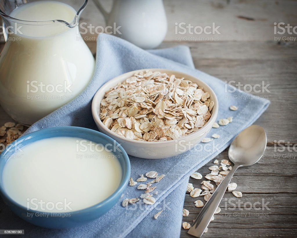 Rolled oats in a bowl and milk stock photo