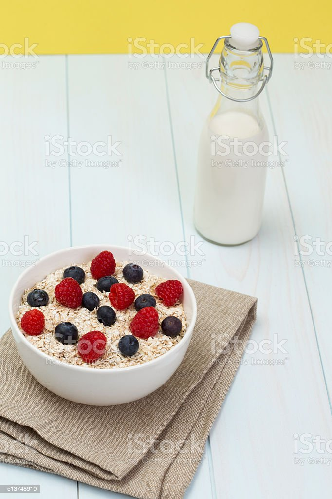 Rolled oats (oat flakes) in a bowl with milk stock photo