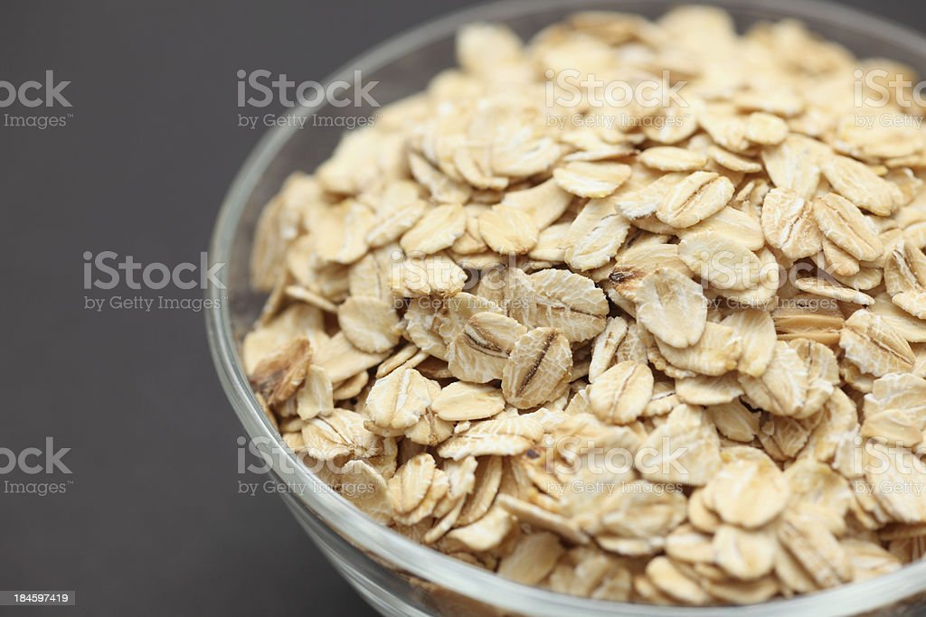 Rolled oats in a glass bowl stock photo