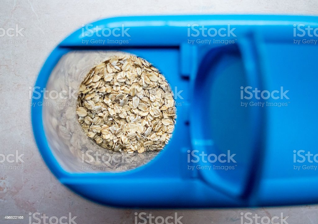 Rolled Oats in a Plastic Cereal Container royalty-free stock photo