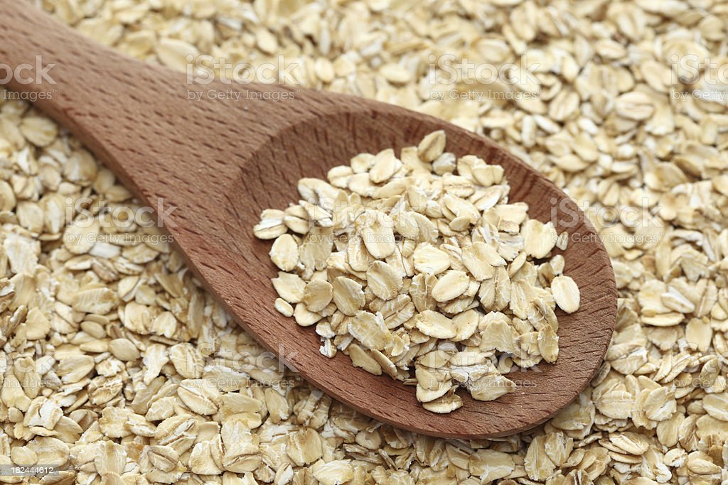 Rolled oats in a wooden spoon stock photo