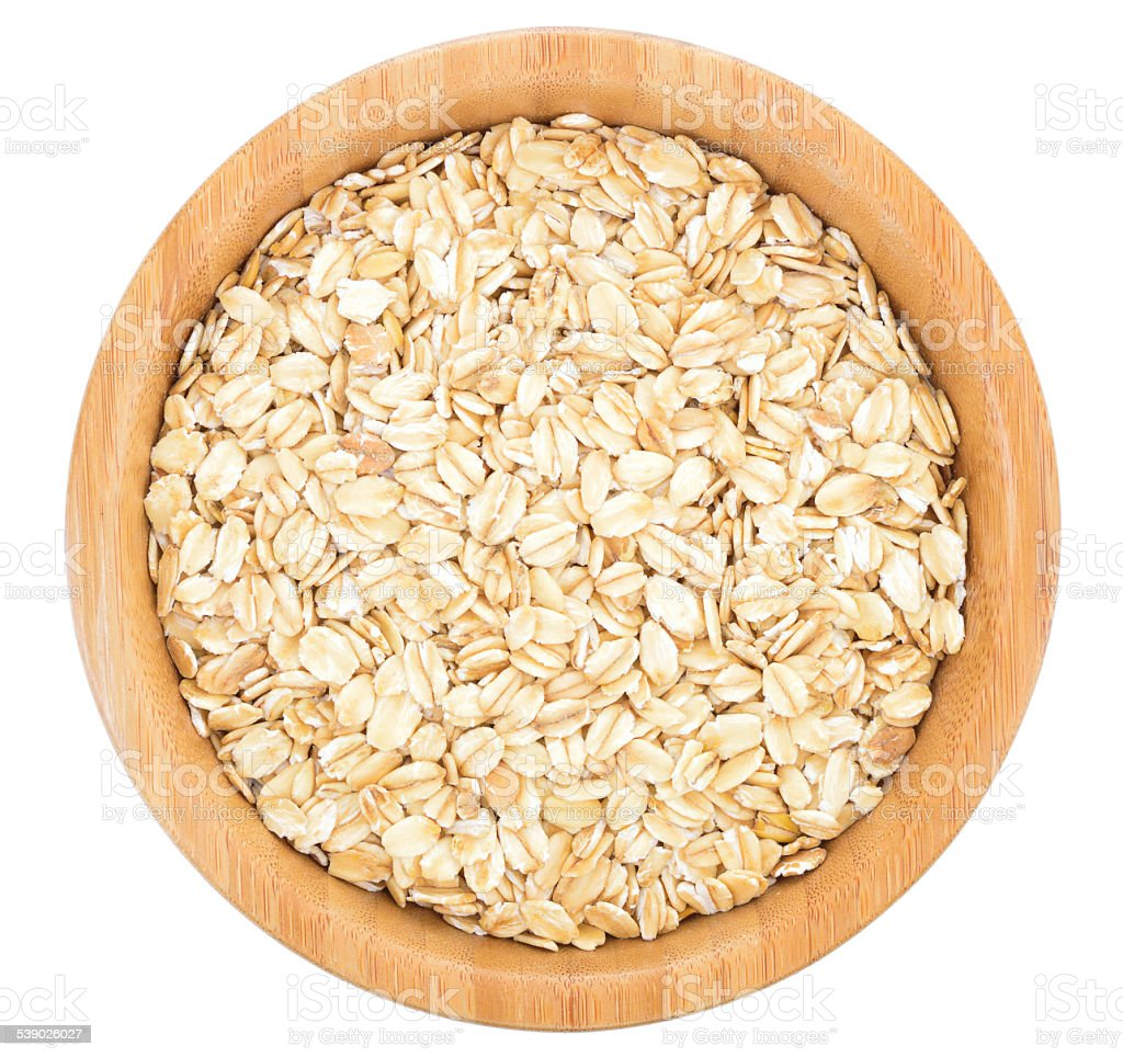 Rolled oats in wooden bowl isolated. stock photo