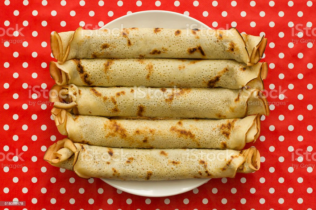 Rolled pancakes served on white plate with spotted tablecloth background stock photo