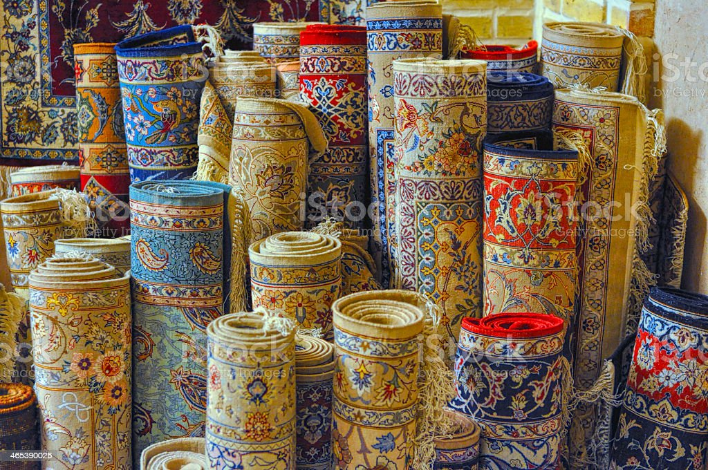 Rolled Persian carpets standing tall in a market stock photo