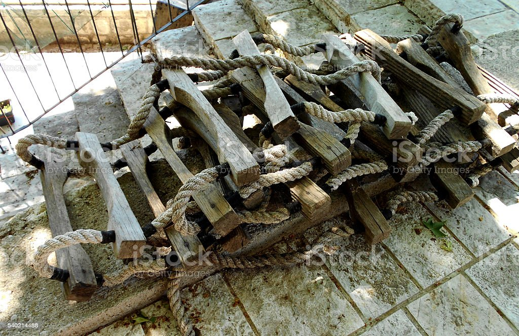 Rolled rope ladder, with wooden bars stock photo