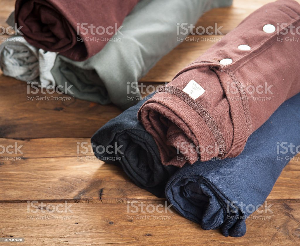 Rolled T Shirts on wood background stock photo