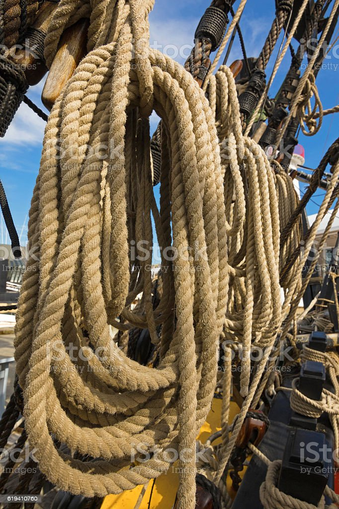 Rolled thick ropes on the old ship near wooden cleats stock photo