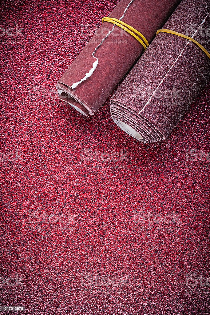 Rolled up emery paper on abrasive sheet stock photo