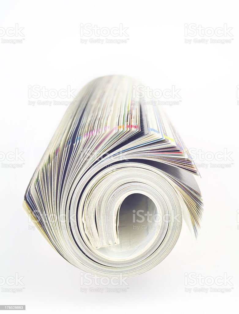Rolled up magazine, newspaper, selective focus, white background royalty-free stock photo
