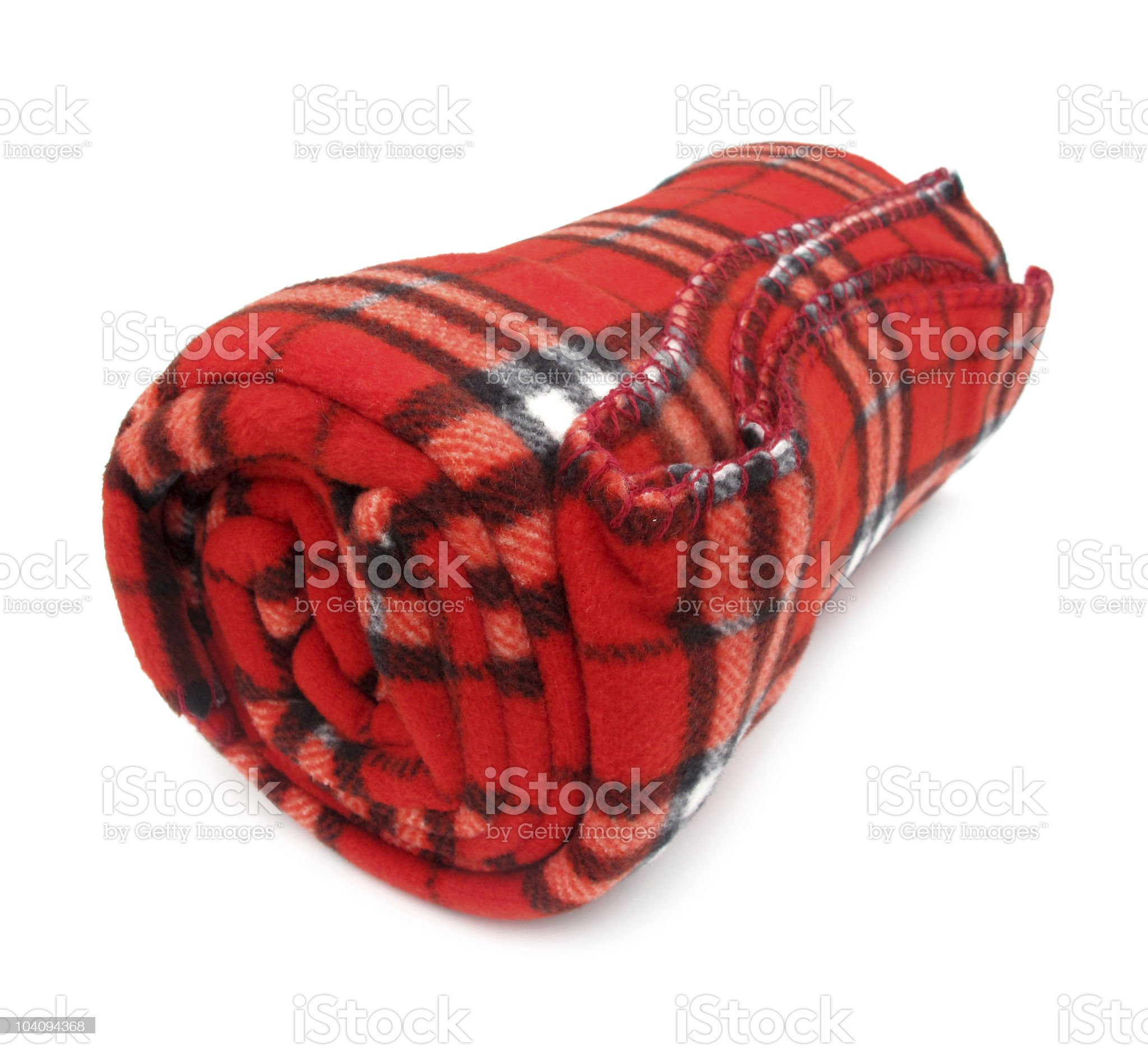 Rolled up red plaid blanket against white background royalty-free stock photo