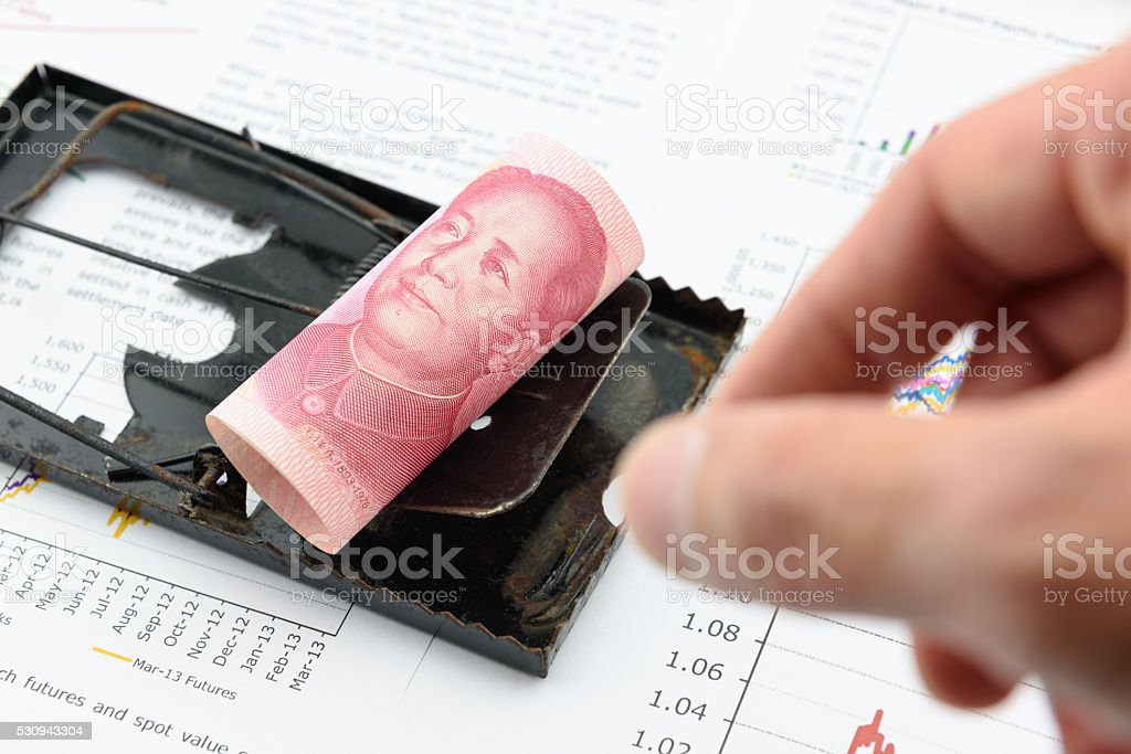 Rolled up scroll of Chinese yuan bill on rat trap. stock photo
