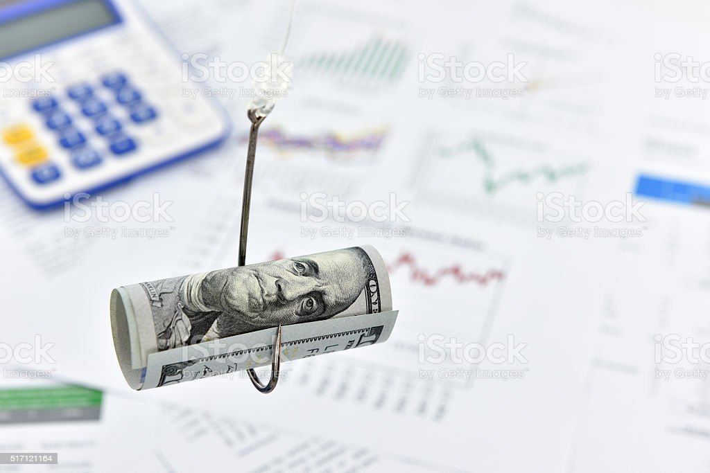 Rolled up scroll of US 100 dollar on a hook. stock photo