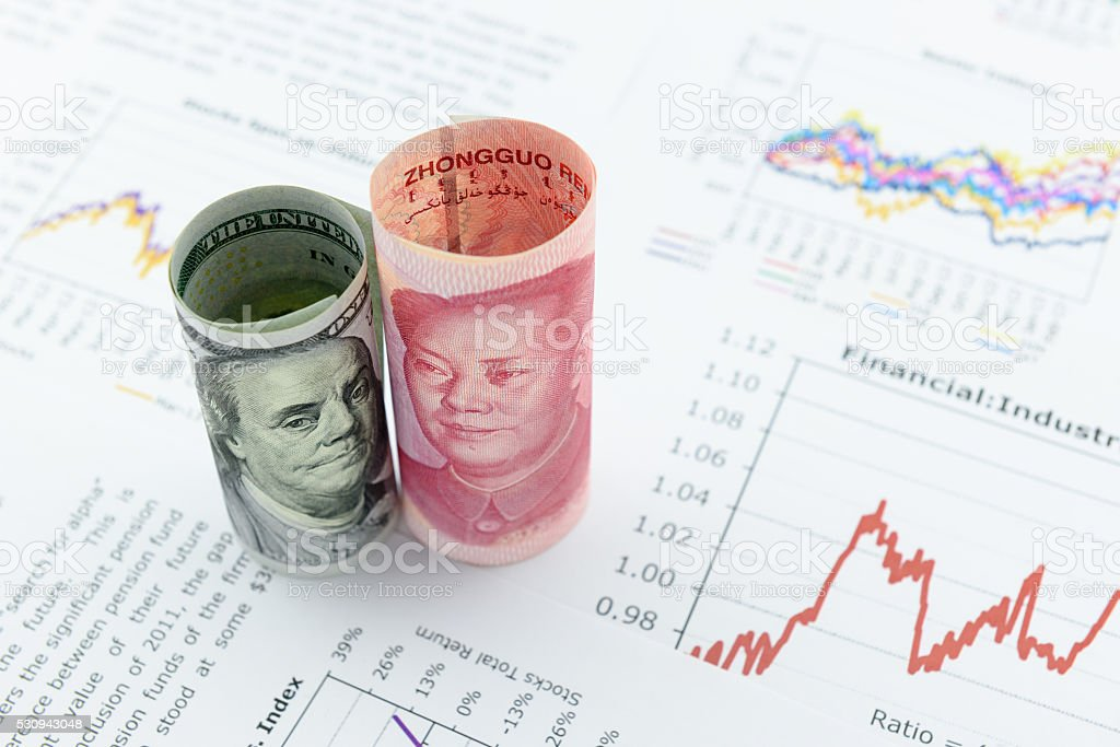 Rolled up scrolls of US dollar bill and Chinese Yuan stock photo
