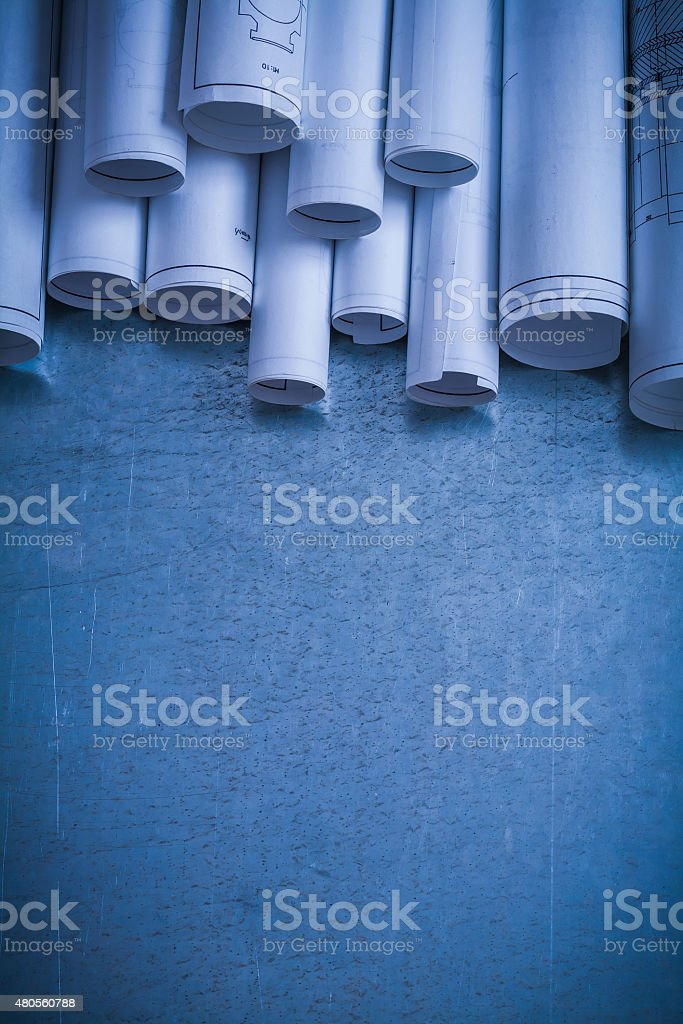 Rolled up white architectural blueprints on scratched metallic s stock photo