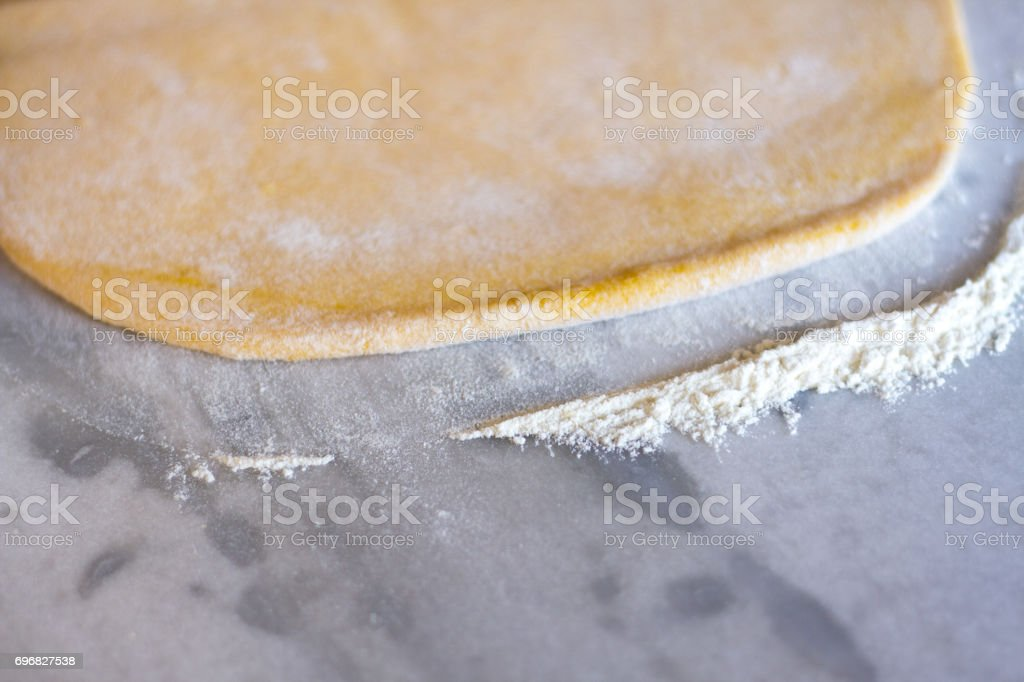 Rolled-Out Dough on Marble Slab (Close-Up) stock photo