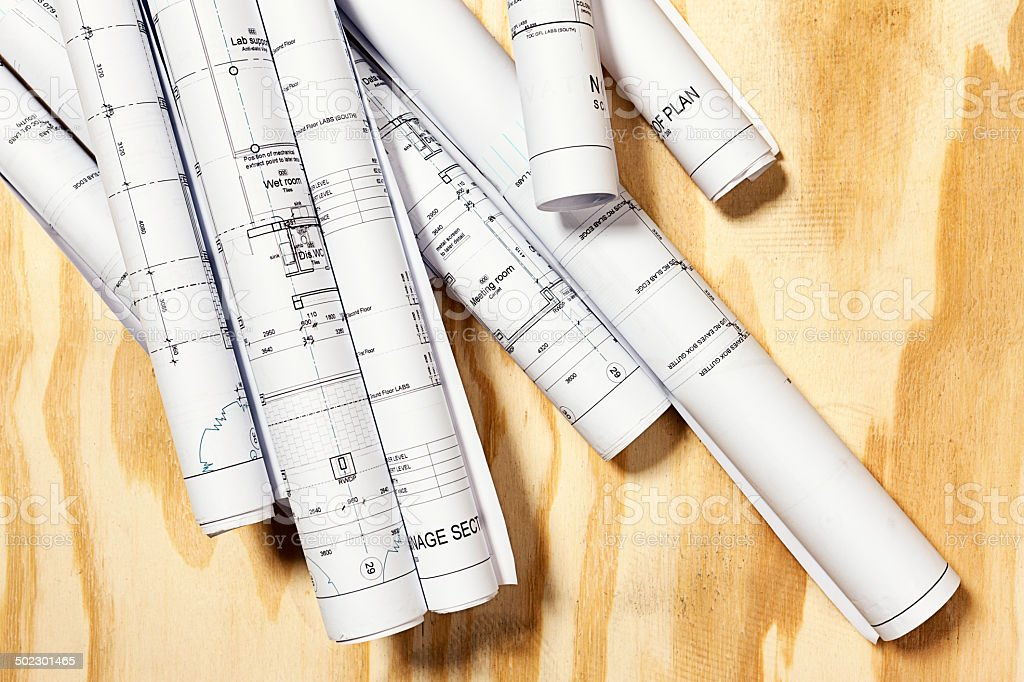Rolled-up building blueprints on wooden background royalty-free stock photo
